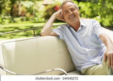 Portrait of relaxed senior man sitting on sofa in backyard
