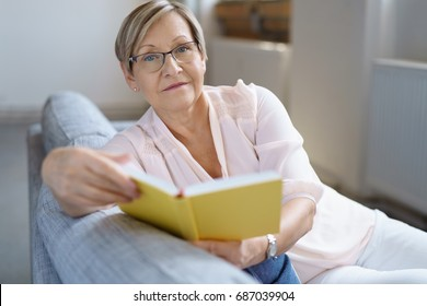 Portrait of relaxed senior woman sitting on sofa with book