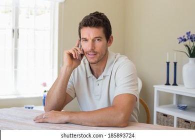 Portrait of a relaxed smiling young man using mobile phone at home