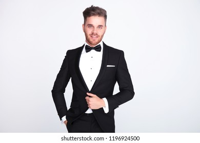 portrait of relaxed stylish man buttoning his black suit while standing on light grey background