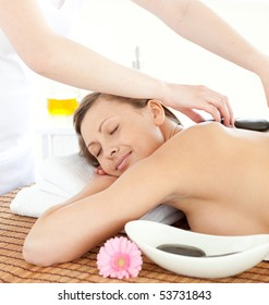 Portrait of a relaxed woman having a massage with stones at the spa