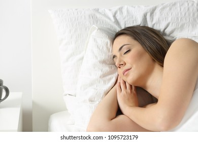 Portrait of a relaxed woman sleeping on a bed