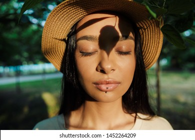 Portrait of relaxed woman wearing lip piercing and straw hat poising with eyes closed and shadow of leaves at her face in green park