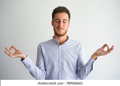 Portrait of relaxed young businessman meditating