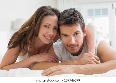 Portrait of a relaxed young couple lying in bed at home
