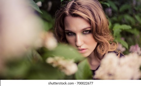 Portrait of relaxed young lady in a summer park waiting. Beautiful young girl with blonde curly hair , outdoor.