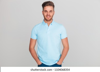 portrait of relaxed young man wearing light blue polo t-shirt while standing on light grey background with hands in pockets