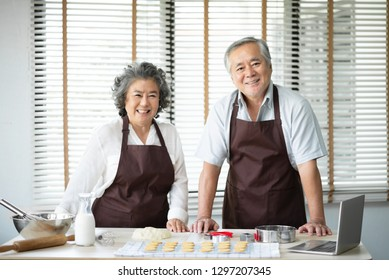 Portrait of Relaxing Asian senior couple in brown aprons standing and preparing for baking cookies. Looking at the camera