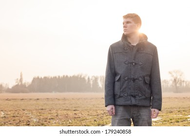 Portrait of relaxing boy in the grass with sunset