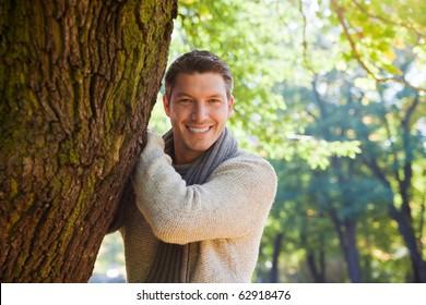 Portrait of relaxing man on tree enjoying golden autumn fall season
