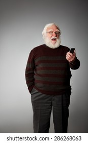 Portrait of relaxing senior man laughing while reading a text message on his mobile phone against grey background