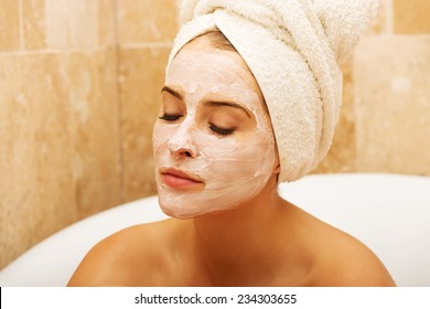 Portrait of relaxing woman with closed eyes and cream lotion on face