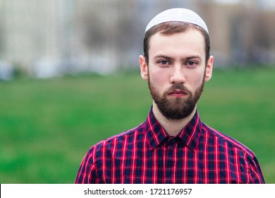 Portrait of religious young Jewish guy in traditional jewish male headdress, hat, boom, or yiddish on his head. Serious Israel man with beard looking at camera outdoors. Copy space, place for text.
