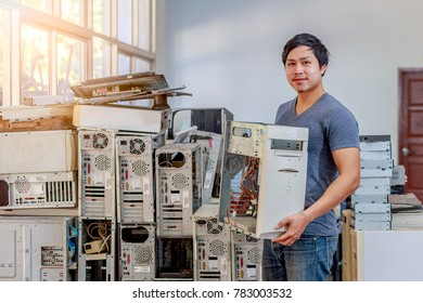 Portrait of repairman with broken pc desktop computer in the background waiting for service, Small business owner of computer repair store