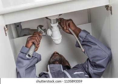 Portrait of a repairman fixing a sink in a kitchen,Handyman