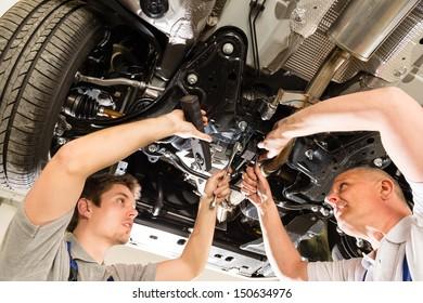 Portrait of repairmen under a car working together