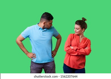 Portrait of resentful dissatisfied couple in casual wear standing together, looking arrogant at each other and arguing, misunderstanding in relations. isolated on green background, indoor studio shot