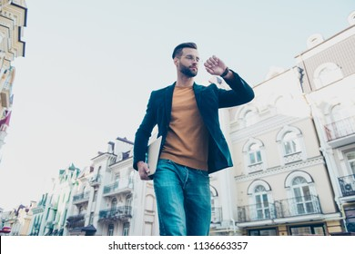 Portrait of responsible serious man holding laptop gadget in hand looking at watch on wrist hurry up for meeting with colleagues. Management employment concept