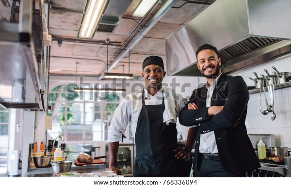 Portrait of restaurant owner with chef in kitchen. Businessman with professional cook standing together and looking at camera.