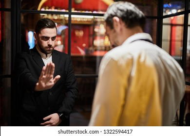 Portrait of restaurant security guard stopping drunk man from entering luxury establishment due to dress code, copy space