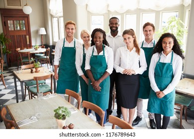 Portrait Of Restaurant Team Standing In Empty Dining Room