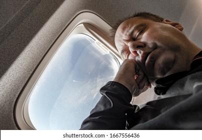 Porträt des ruhenden Passagiers im Flugflugzeug. Der müde Mann schlief mit dem Fenster im Flugzeug. Entspannen Sie sich auf dem Weg in einem Flugzeug, Nahaufnahme.