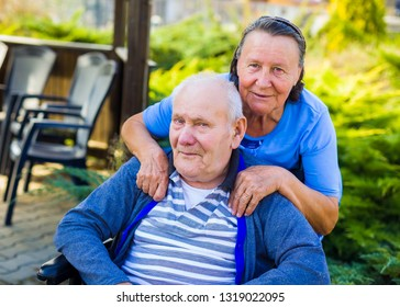 Portrait of retired caring wife and her paralised happy husband.