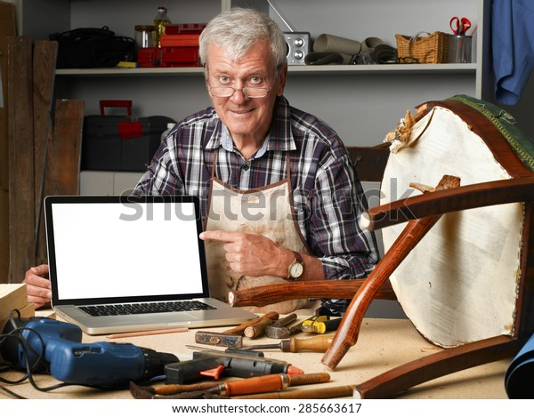 Portrait of retired carpenter points out of laptop while sitting in his workshop next to the broken legged chair. Small business.