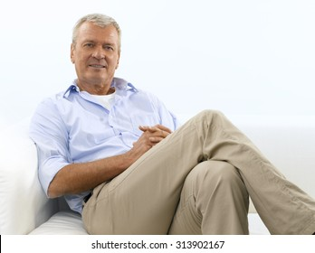 Portrait of retired old man sitting at sofa and smiling. Isolated on white background.