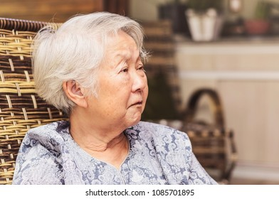 Portrait of a retired old woman seated with a concerned or sad expression. Japanese descendant, aligned to the left.