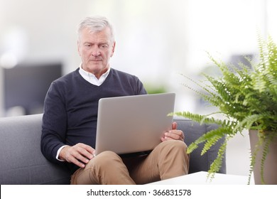 Portrait of retired professional man using laptop while working at home.
