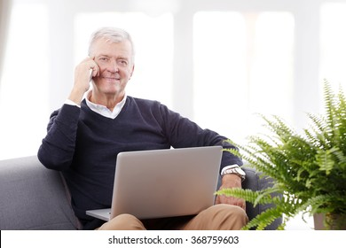 Portrait of retired senior man sitting at home and working online with laptop while making call.