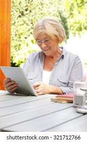 Portrait of retired woman holding in her hands digital tablet and reading emails while sitting at nursing home garden.