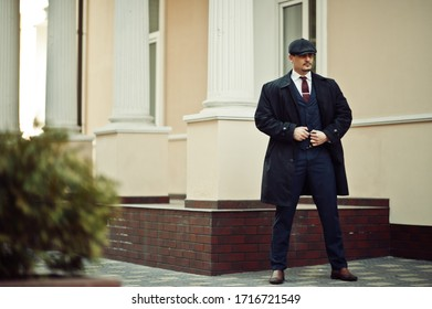 Portrait of retro 1920s english arabian business man wearing dark coat, suit, tie and flat cap.