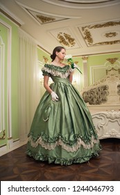Portrait of retro baroque fashion woman wearing green vintage dress at old palace interior