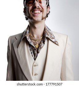Portrait of a retro man with a gold tooth in a 1970s leisure suit and sunglasses smiling to the camera
