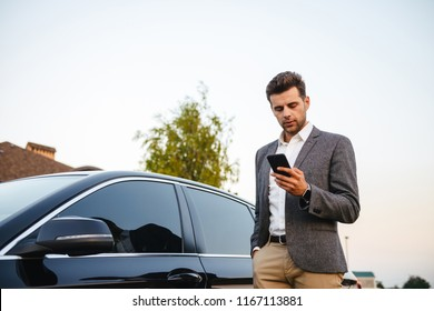 Portrait of rich businessman wearing suit, standing near his luxury black car and using smartphone while holding in hand