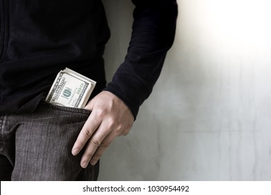 Portrait a rich guy: Dollars money in a pocket jeans. Handsome man has a lot of money. He is a investor of business. Cool guy get successful of his business. He can earn a lot of money with copy space