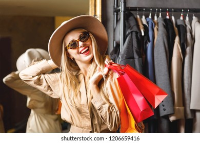 Portrait of rich pretty blonde shopaholic woman wearing sunglasses and fashion hat standing and smiling with colored shopping bags in fashion mall, concept of consumerism, Black Friday, sale, rich