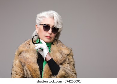 Portrait of rich woman in fur coat and sunglasses looking at camera. Beautiful lady in white expensive gloves posing in studio. Pret-a-Porter or High Fashion.