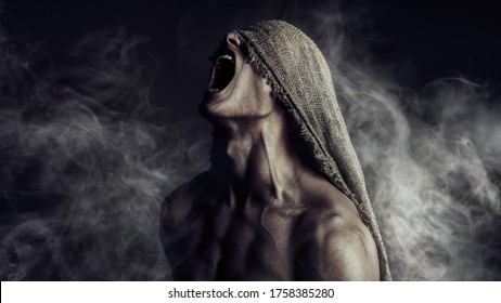 Portrait of a roaring muscular man with burlap on his face, expressing rage and suffering. Studio shot on a black background with smoke. Horrors and Halloween.