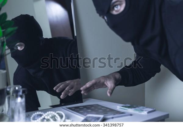 Portrait of robber in black mask during burglary