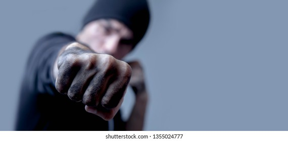 Portrait of robber giving a punch and ready to robbery the money. Aggression, gangsterism concept. Selective focus on fist.