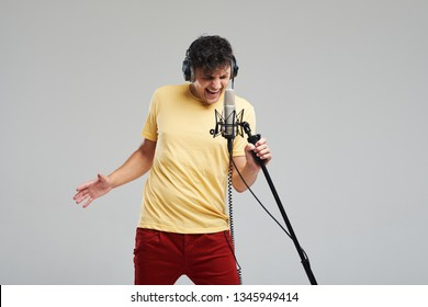 Portrait of rock singer man in studio professional headphones keeping static acoustic mic, sings a song loudly on grey background. Concept of rock music and rave