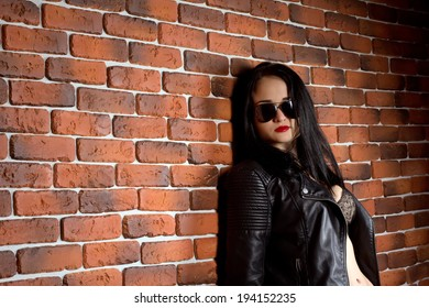 Portrait of rocker girl in black leather jacket over red brick wall