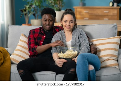 Portrait of the romantic attractive young Caucasian couple talking cheerfully, eating popcorn and watching TV at home.