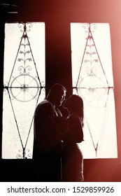 portrait of a romantic couple in a backlight from a window or door, silhouette of a couple in a doorway with a backlight, couple of lovers groom and bride at the window, girl holding flowers in hands