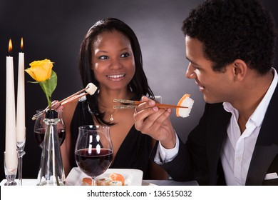 Portrait Of Romantic Couple Eating Sushi At Dinner