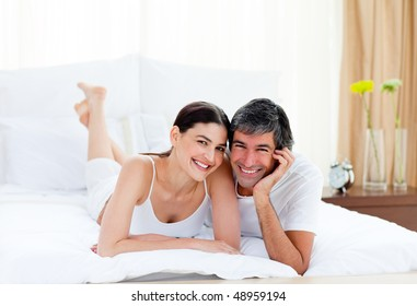 Portrait of a romantic couple embracing lying on their bed