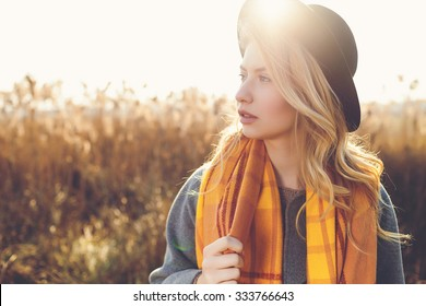 Portrait of romantic girl in a field in sunset light. winter, autumn life